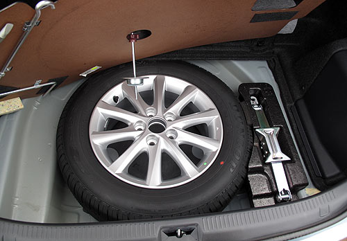 The Hybrid Camry comes with a full-size spare and included in the kit you'll find with the spare is a towing hook that has to be attached before the vehicle can be towed with a strap.